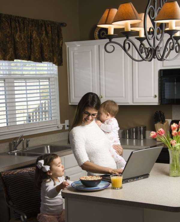 Mother holding baby and typing on laptop computer with girl eating breakfast in kitchen.