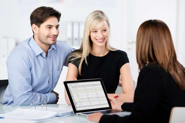 Couple Smiling While Looking At Financial Advisor At Desk